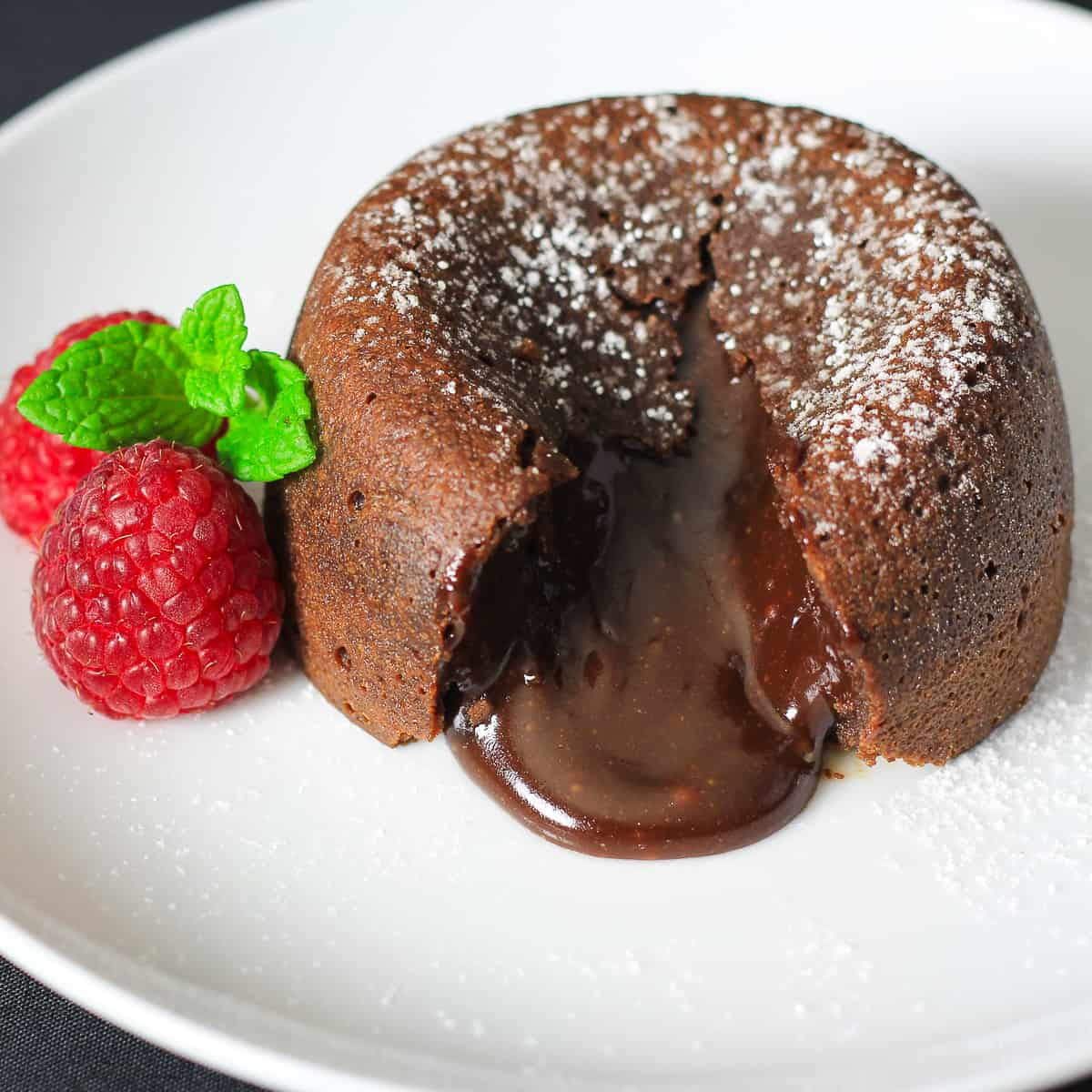 cut open chocolate lava cake with powdered sugar on top and raspberries and mint beside it.