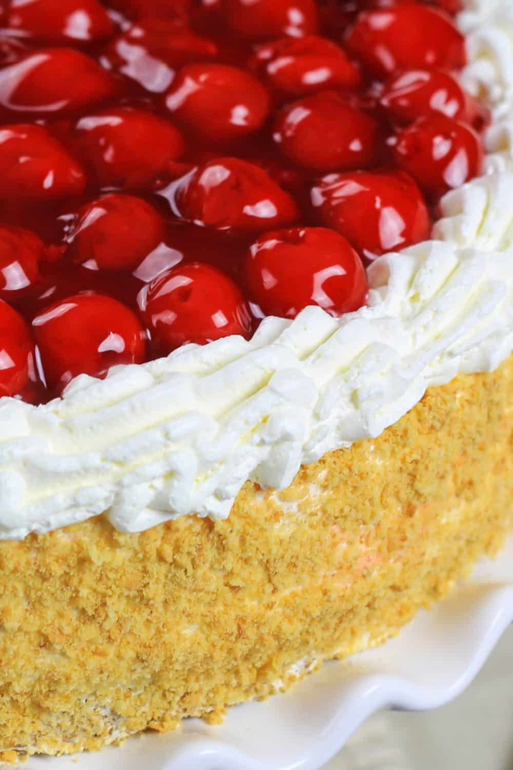 Up close picture of a completed cherry jello cake recipe with the cake sitting on a white cake plate and topped with cherry pie filling, cream cheese filling, and a coating of cake crumbs around the edges