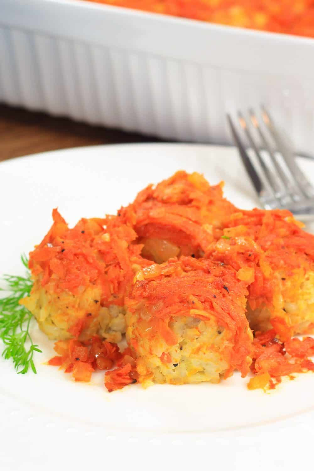 Close up picture of stuffed cabbage rolls topped with shredded carrots laying on a white plate in front of a large white casserole dish containing more of the rolls topped with sprigs of fresh herbs
