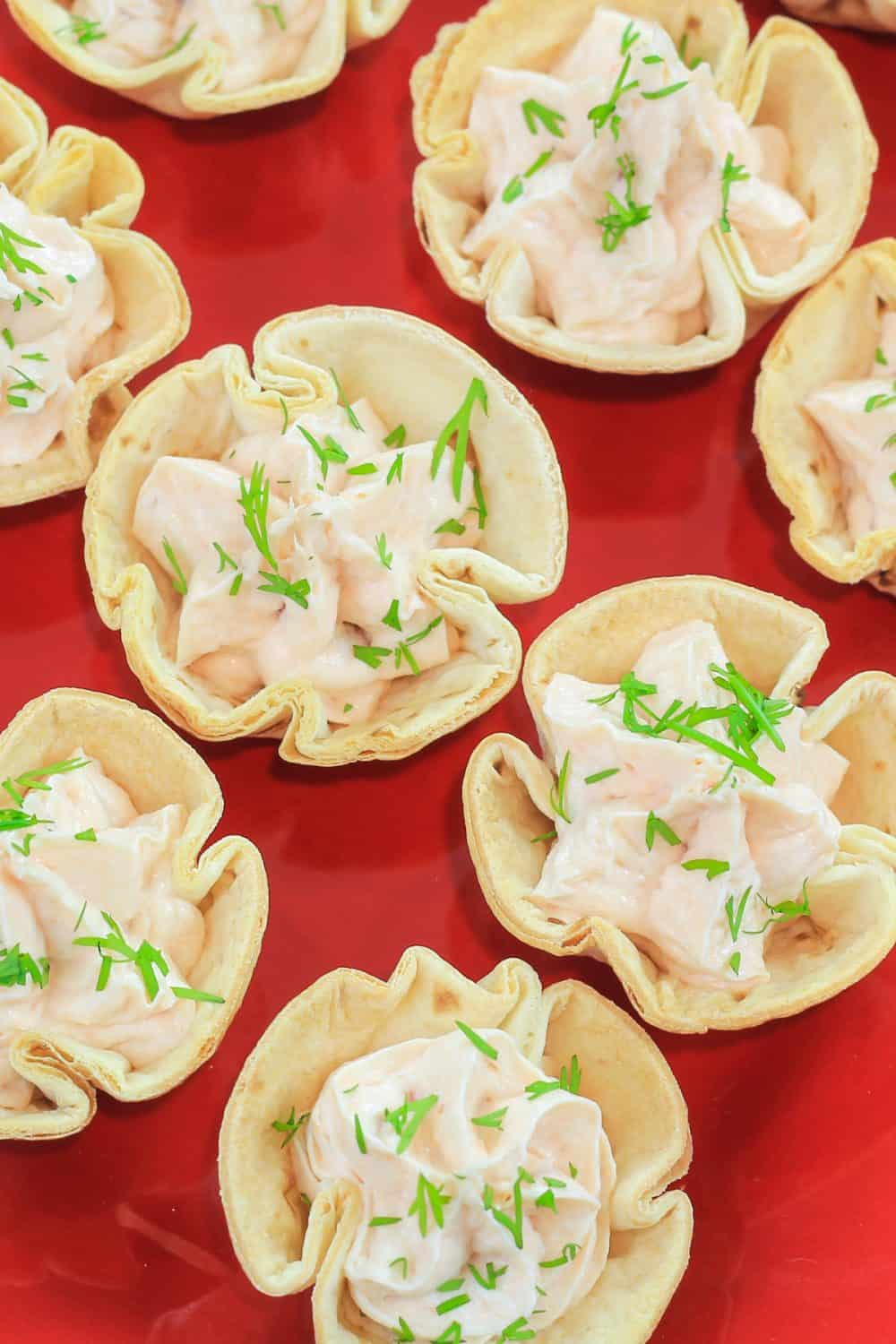smoked salmon appetizer cream cheese tortillas cups on a red plate