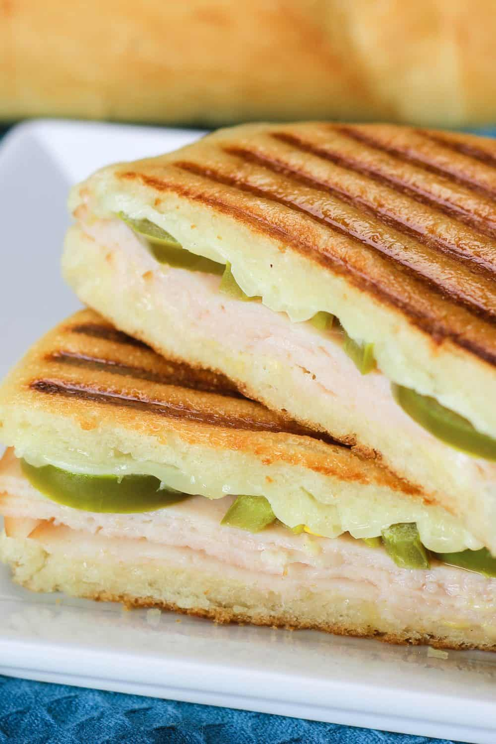 Close up picture showing a sliced turkey panini recipe on a white plate that is sitting on a blue cloth with fresh bread in the background
