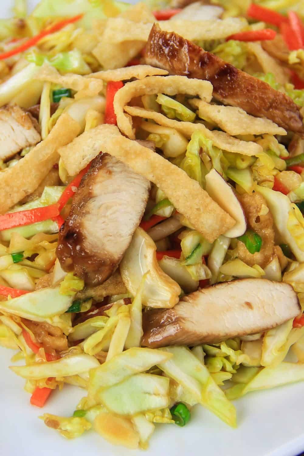 close up image of an asian chicken salad with cooked chicken, shredded cabbage, carrot, cashews, and crispy wontons