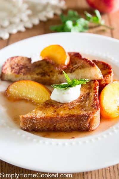 french toast with peaches, creme friache, and a mint leave on top