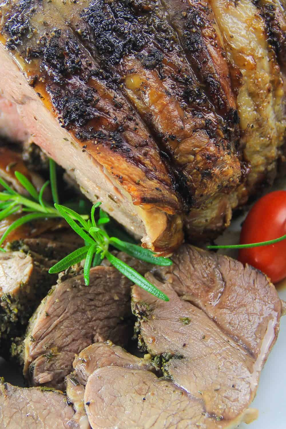 boneless roasted leg of lamb with rosemary and cherry tomato next to it