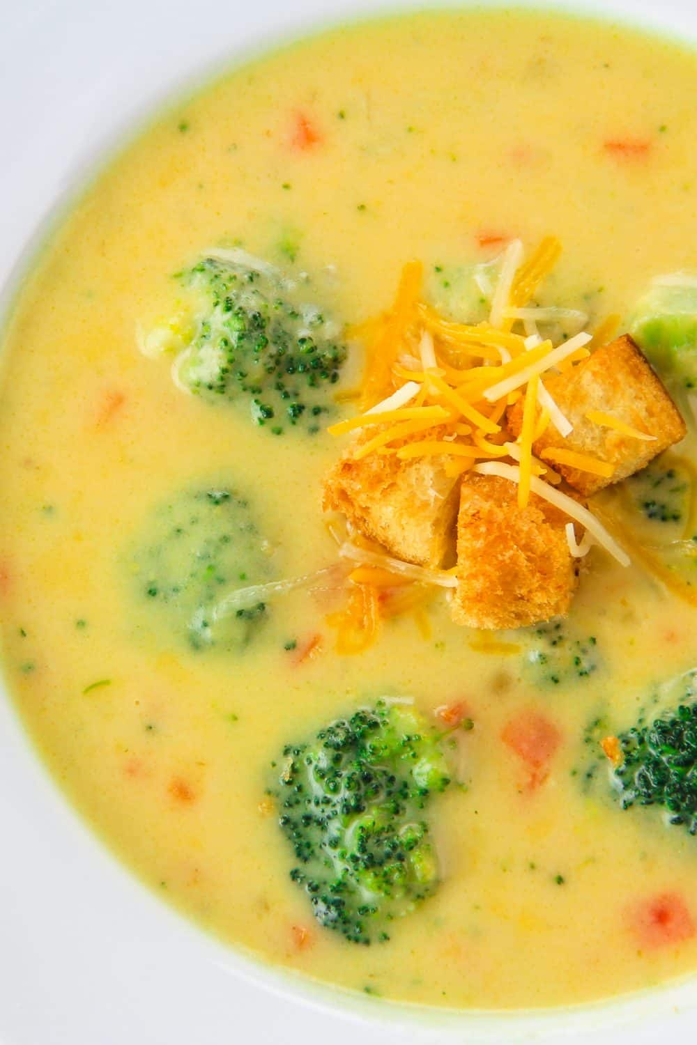 Overhead picture of a white bowl filled with panera bread broccoli cheddar soup recipe topped with croutons and shredded cheese