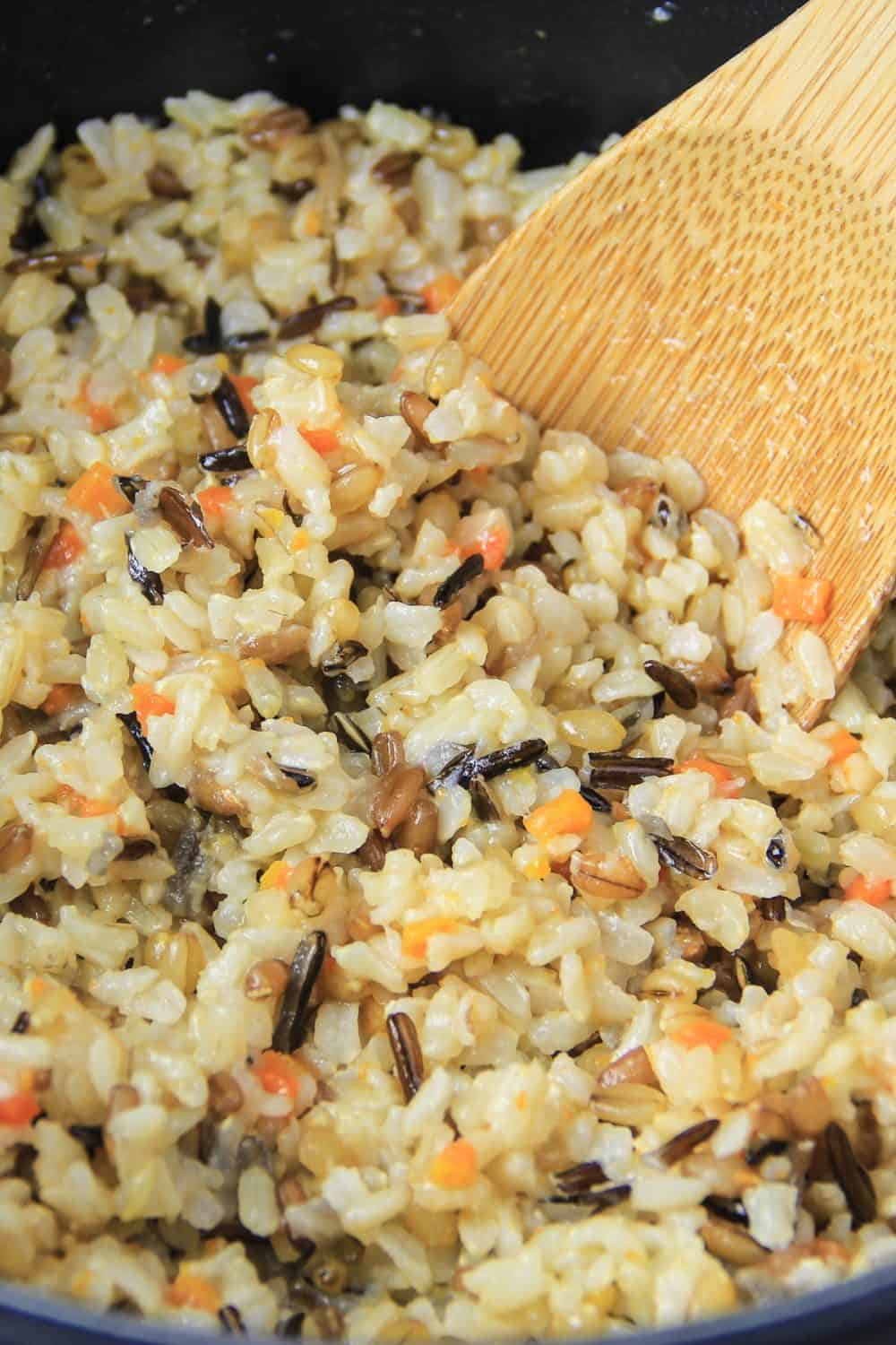 A wooden spoon stirs wild brown rice in a skillet