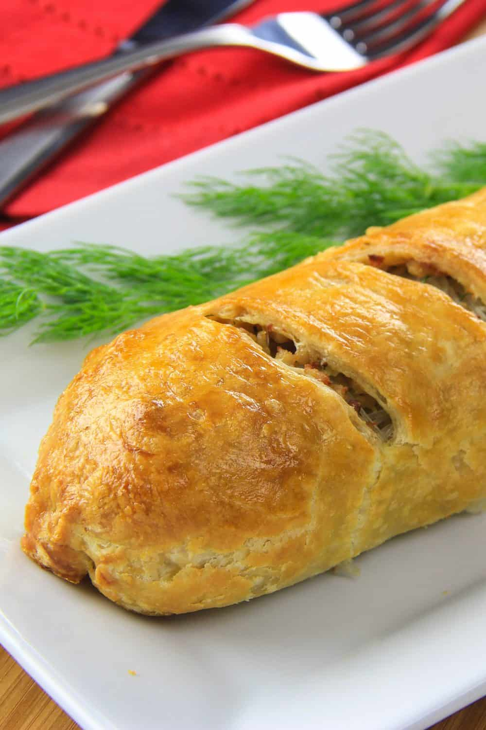 Prepared chicken puff pastry served on a white plate with fresh dill and a red napkin with fork and knife