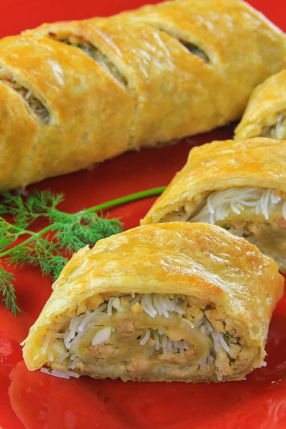 Prepared chicken puff pastry stuffed with rice noodles, eggs, dill, and ground chicken presented on a red plate with fresh dill as a garnish