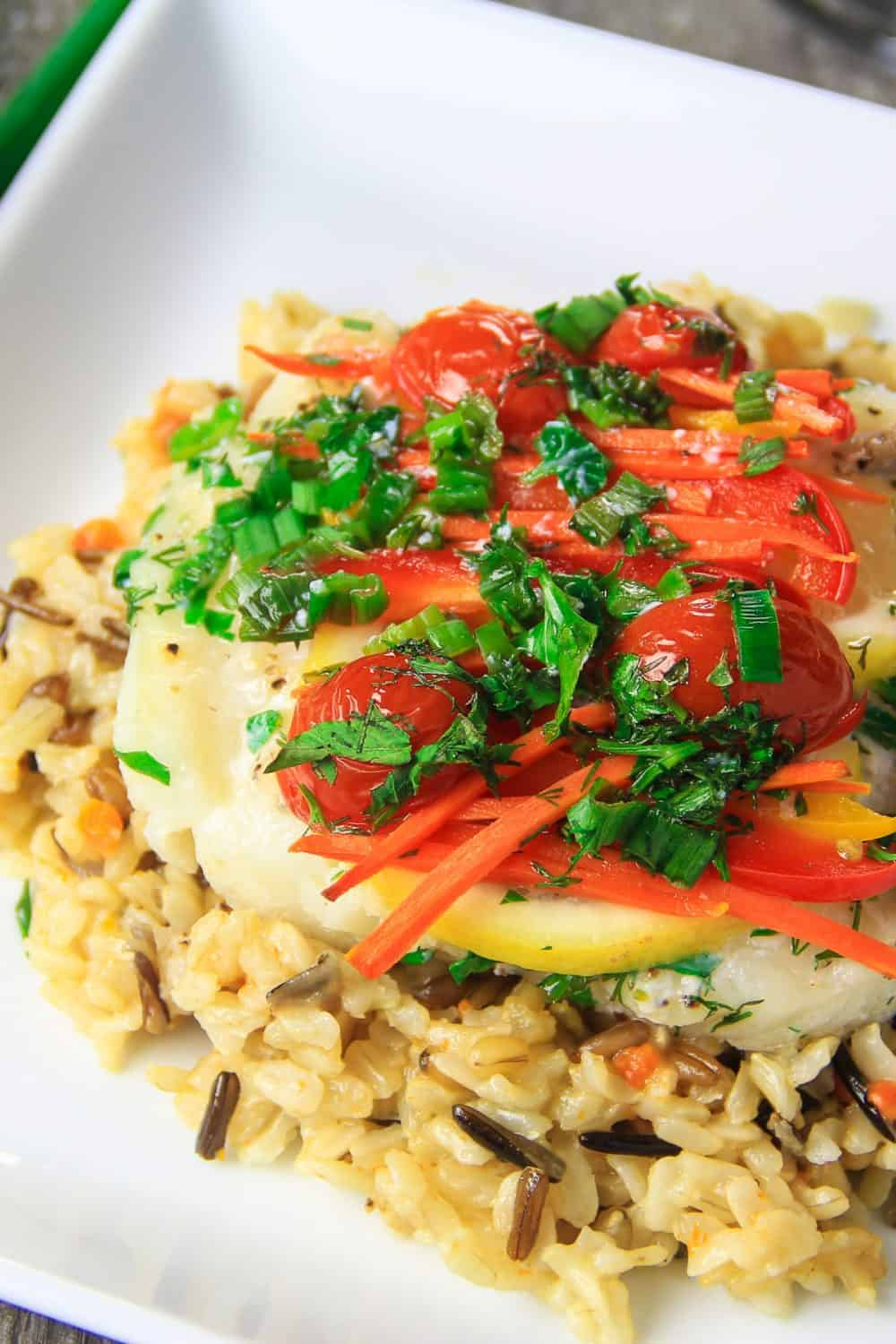 baked cod on a plate with lemon and roasted peppers and tomatoes
