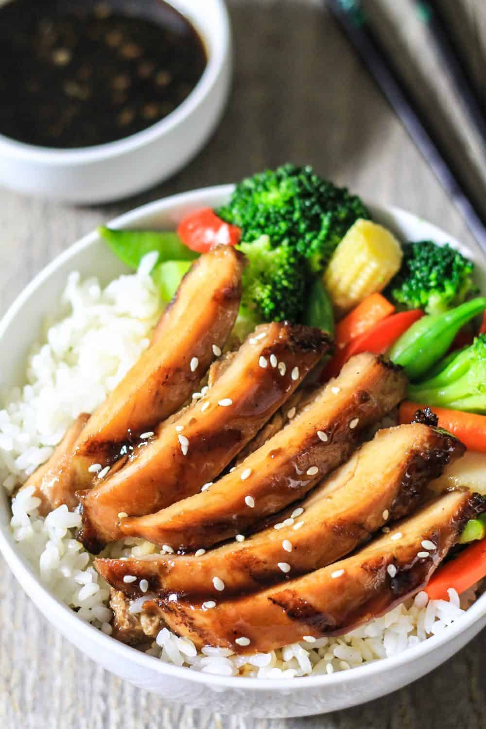 Grilled teriyaki chicken on white rice with fresh vegetables