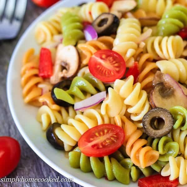 Tri color pasta salad with mushrooms, olives, cherry tomatoes, red bell peppers, red onions, and Italian dressing