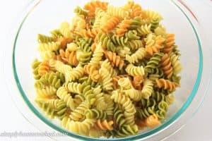 cooked tri color pasta in a glass bowl