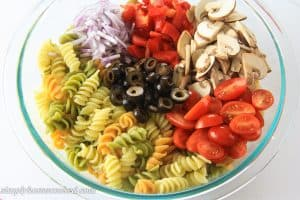 tri color pasta, red peppers, mushrooms, red onions, olives, and cherry tomatoes together in a glass bowl