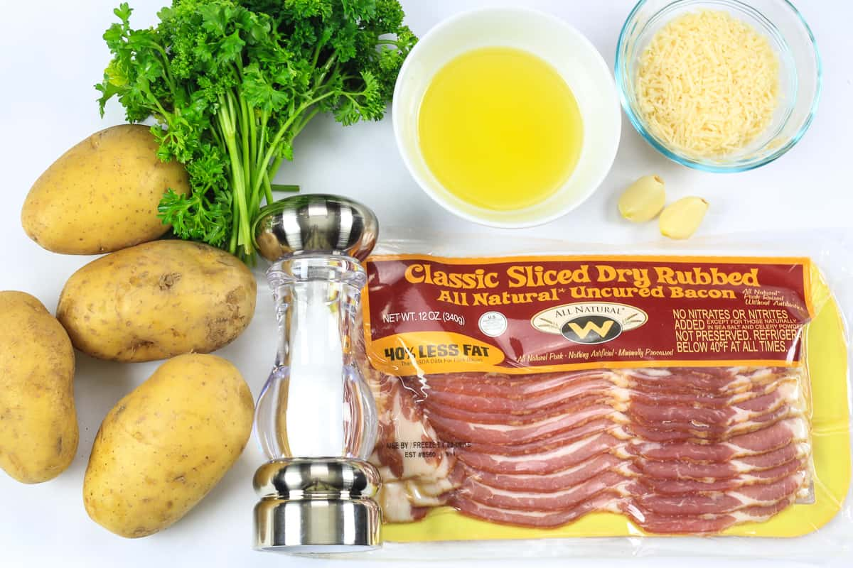 an overhead photo of ingredients needed for roasted potatoes with bacon and parsley, and parmesan