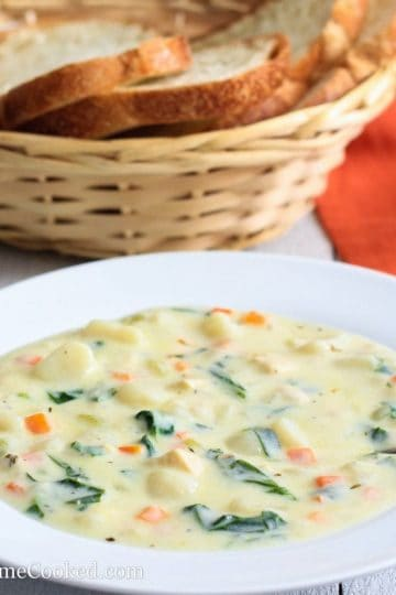 Chicken Gnocchi Soup in a white bowl with a basket of sliced bread behind it
