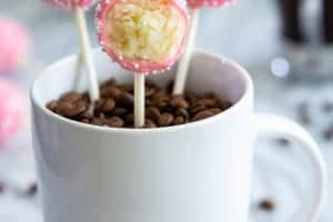 pink cake pops in a white mug filled with coffee beans