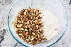 chopped almonds and flour in a glass bowl.