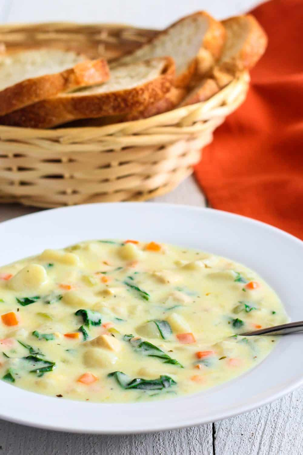 creamy chicken gnocchi soup with carrots and spinach in a white bowl with a basket of sliced bread beside it
