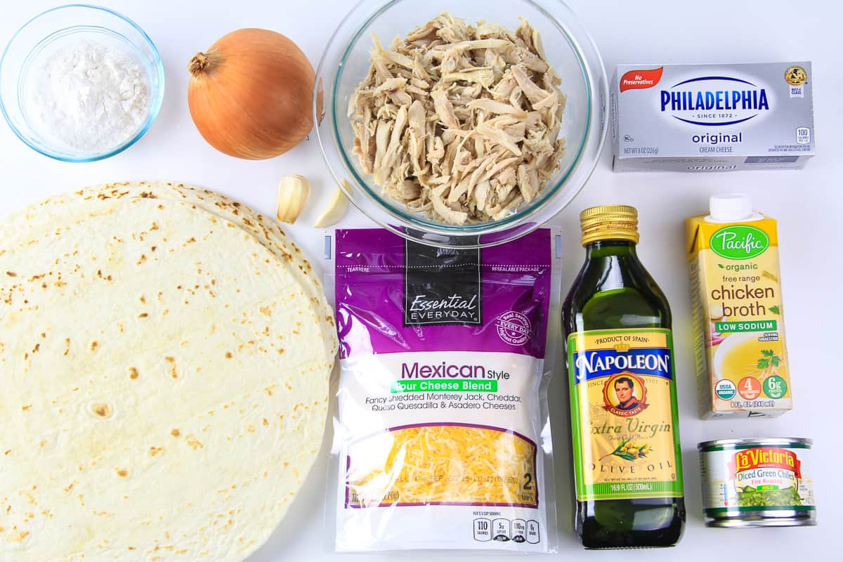 Ingredients for cheesy chicken enchiladas laying on a flat white surface photographed from overhead.