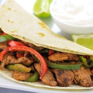chicken fajitas on a white plate with a bowl of sour cream and to limes next to it