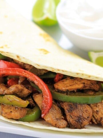 Chicken Fajitas with bell peppers and sour cream on a plate