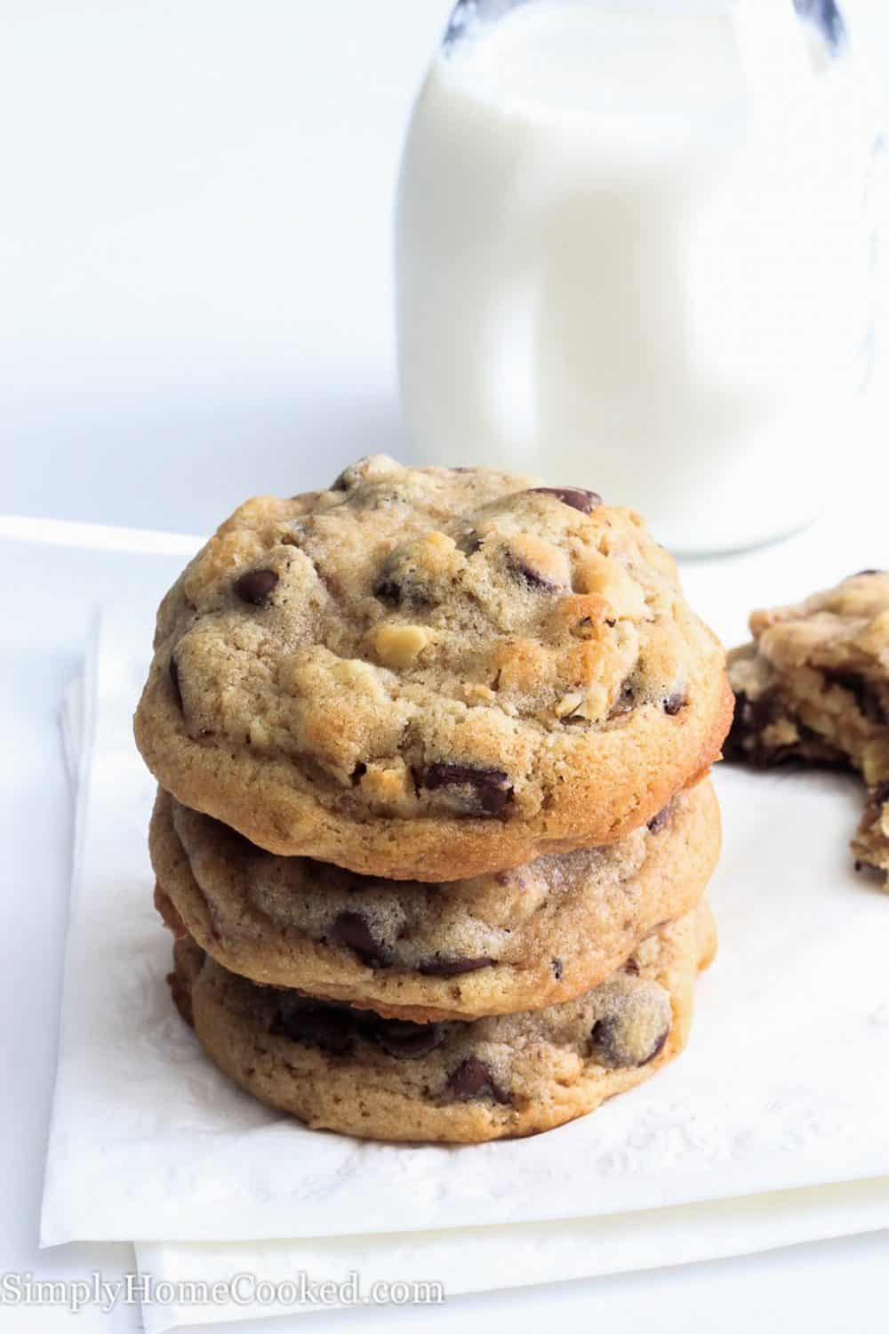 Stack of chocolate chip walnut cookies on a white napkin that is laying on a white surface with a glass jar of milk sitting in the background