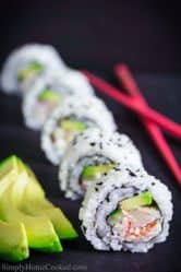 sliced shrimp tempura sushi roll with sliced avocado on the side along with red chopsticks