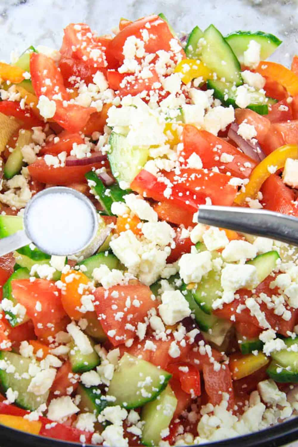 close up image of a salad with cucumbers, tomatoes, bell peppers, and feta cheese on top