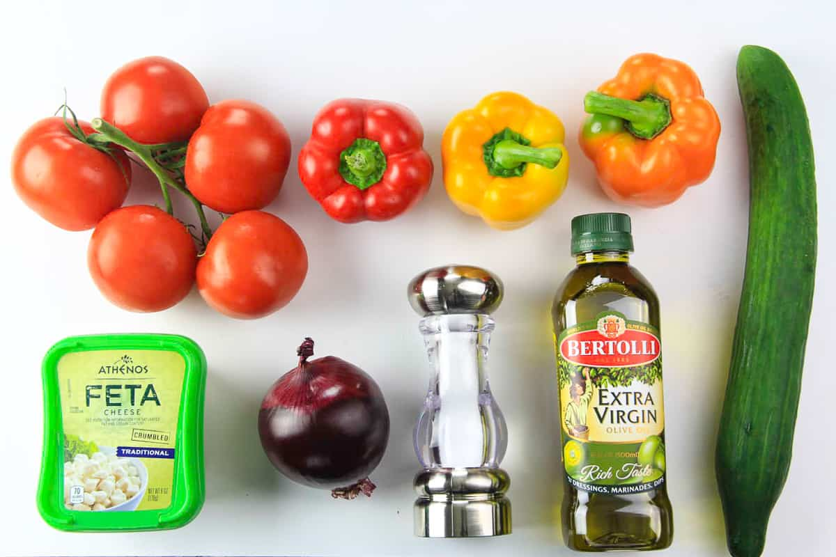 an overhead image of ingredients needed for a cucumber tomato feta salad