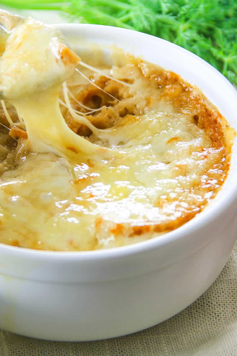 A close up of a cheese pull showing the broiled cheese on top of the french onion soup.