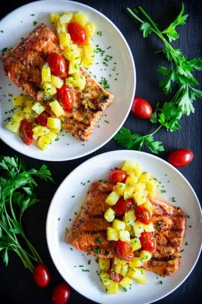 grilled salmon with sautéed cherry tomatoes and pineapple on top, with parsley beside it.
