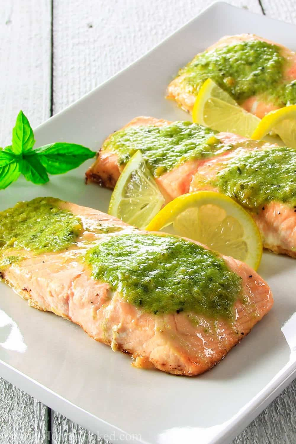 Baked salmon fillets with pesto butter on top, and a sliced lemons and basil on the side