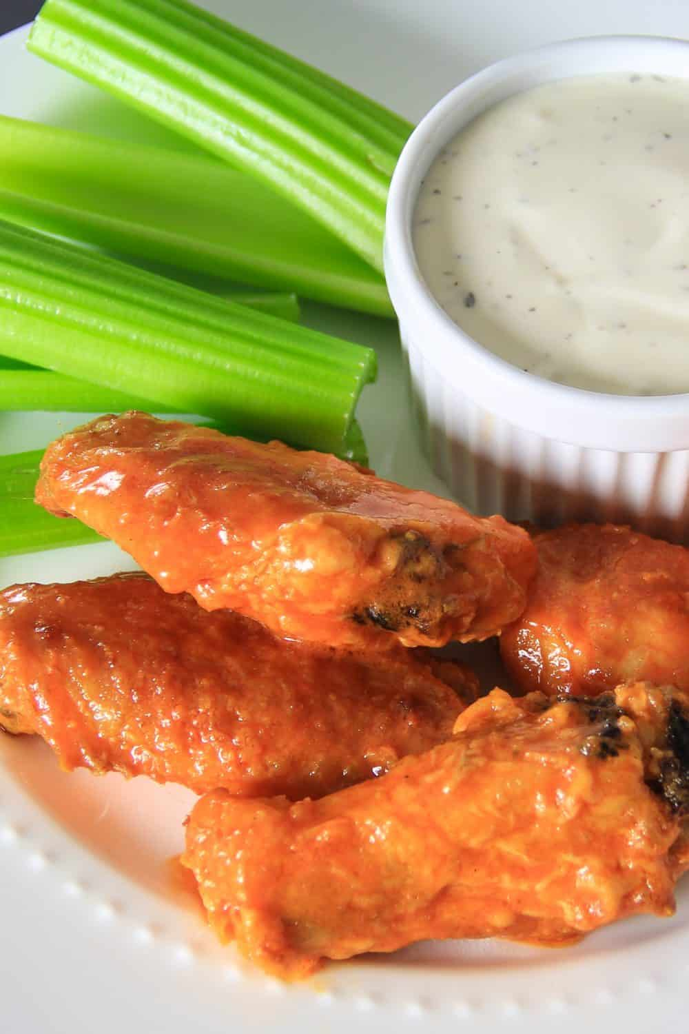 Overhead picture taken of a large white plate with multiple baked chicken wings, slices of celery, and a bowl of dipping sauce