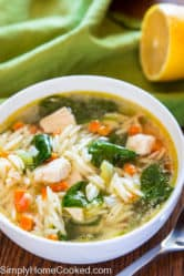 lemon chicken orzo and spinach soup in a white bowl with a green napkin and sliced lemon beside it