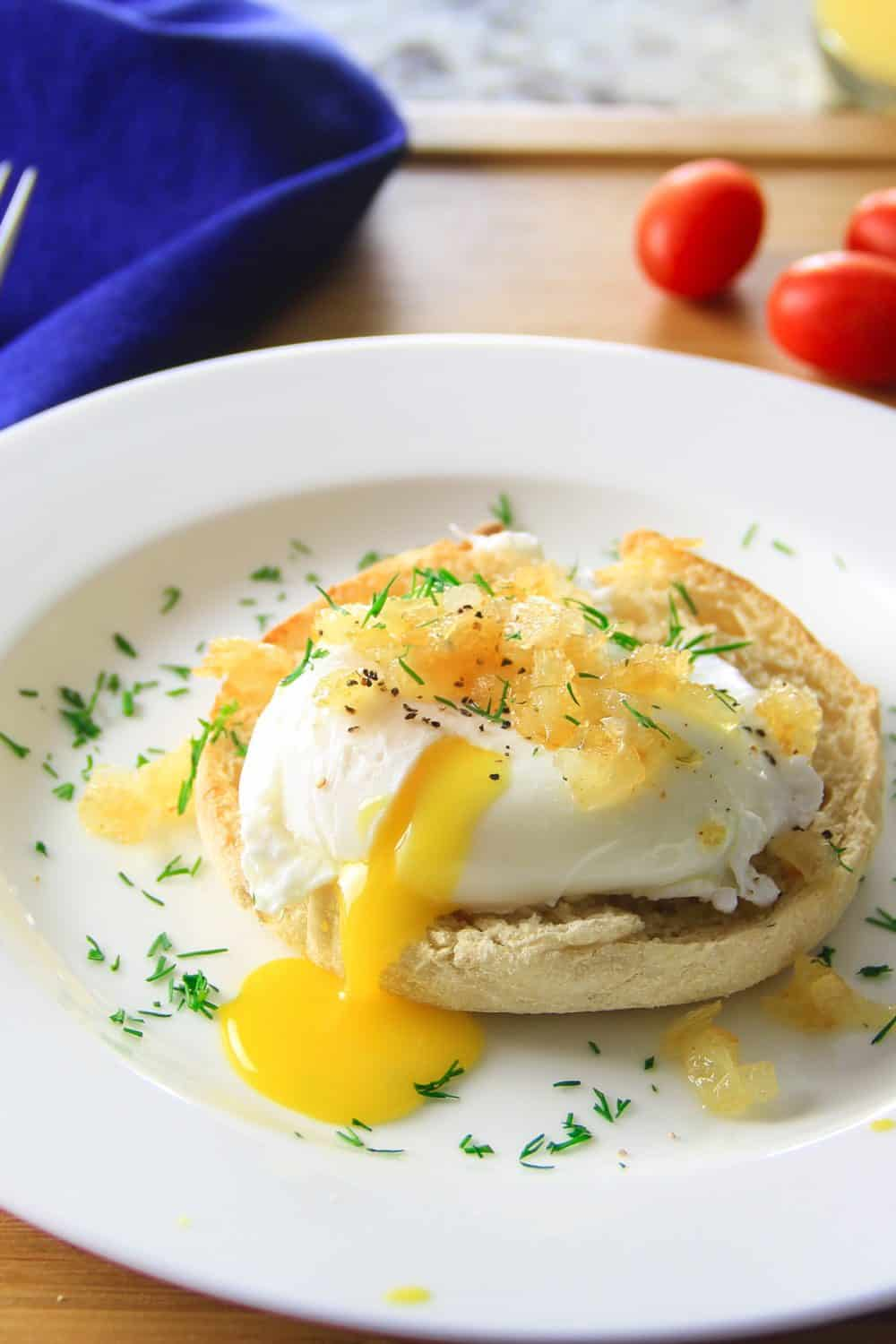 Close up of poached egg with caramelized onions on an English muffin, on a white plate with a blue napkin and grape tomatoes in the background.