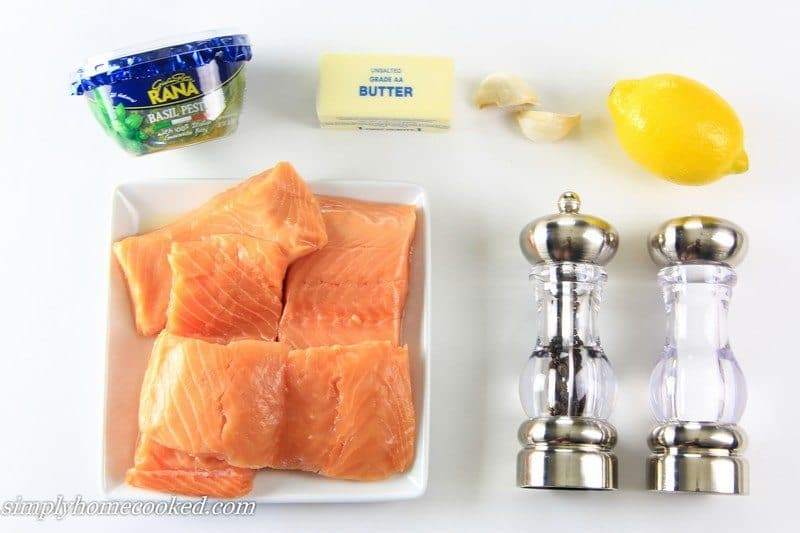 an overhead image of baked pesto salmon ingredients on a white background