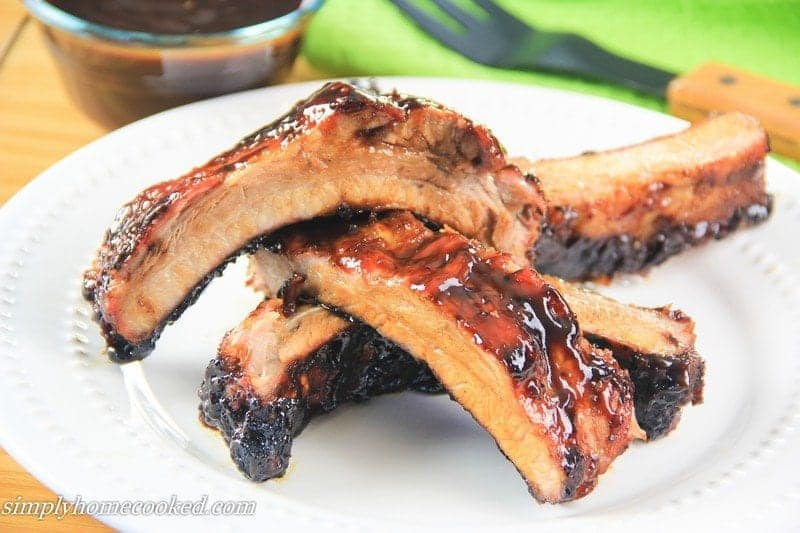 barbecue pork ribs stacked on each other on a plate