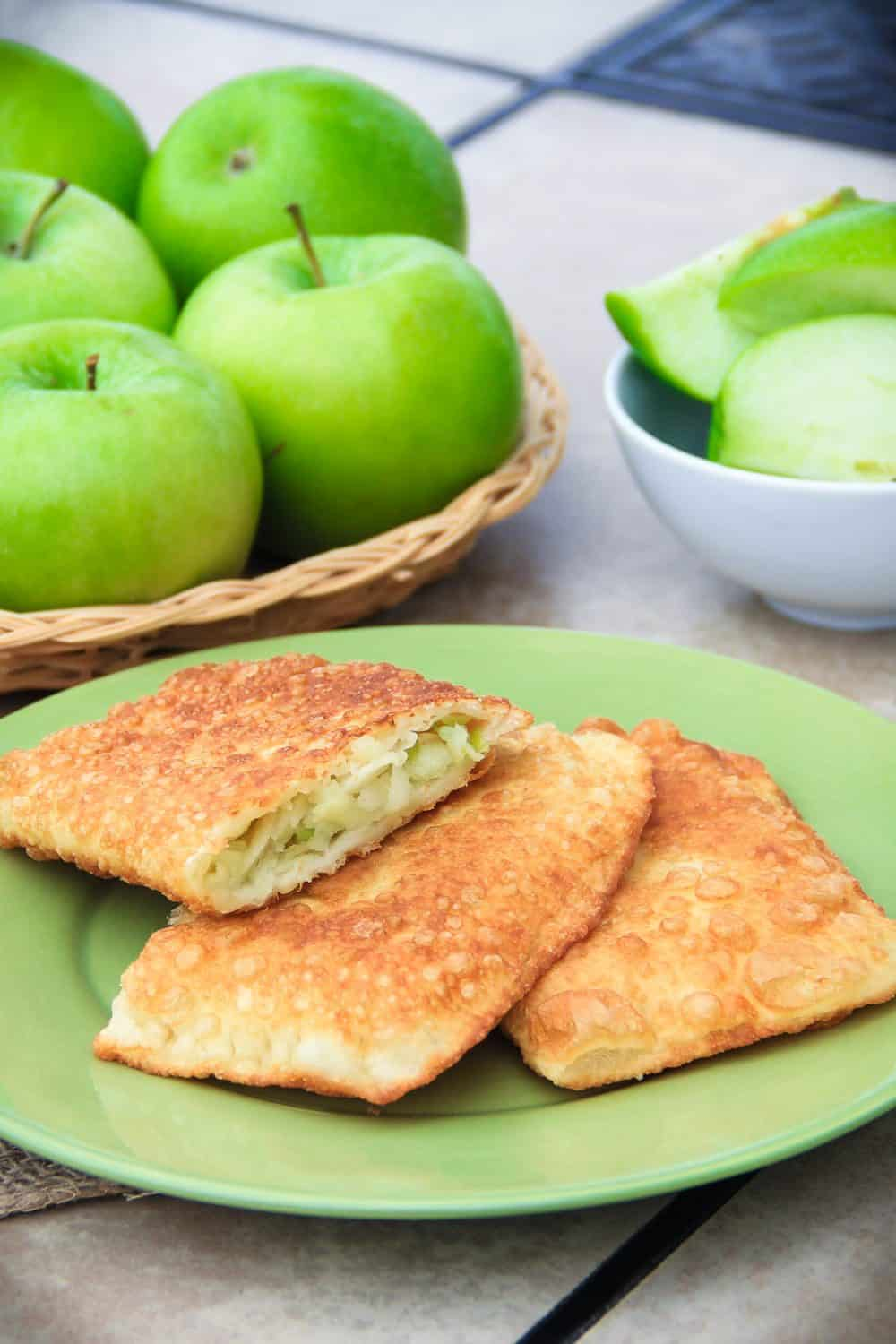 from scratch made apple turnovers on a green plate with sliced granny smith apple wedges in the background