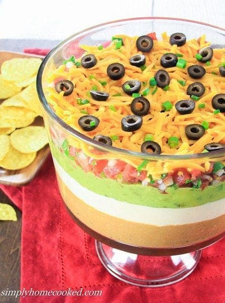 7 layer dip with olives, cheese, guacamole, sour cream, pico de gallo and with some chips