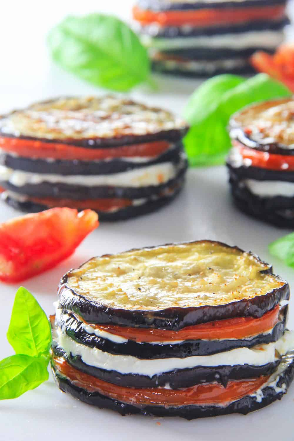 eggplant napoleon stacked with slices eggplant, sliced tomato, and sliced mozzarella cheese. with basil beside it