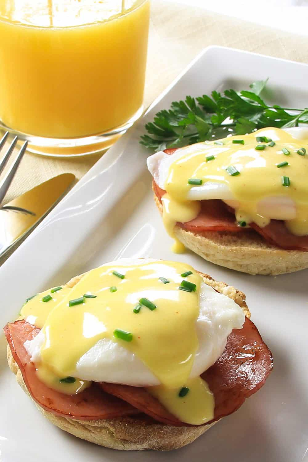 eggs Benedict on a white plate with a glass cup of orange juice beside it