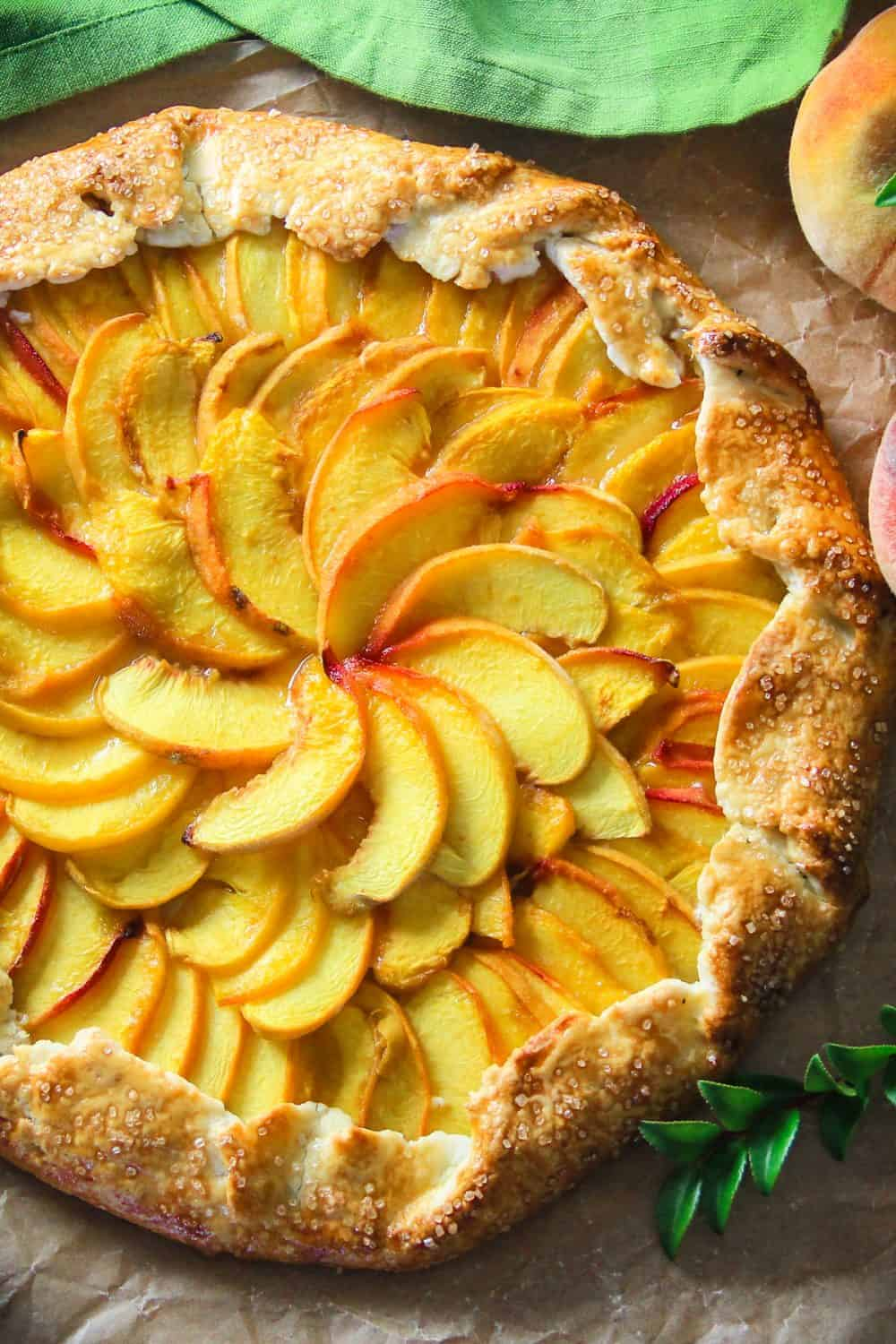 Overhead image of the peach galette laying on a brown paper surface with fresh peaches and a green napkin in the background