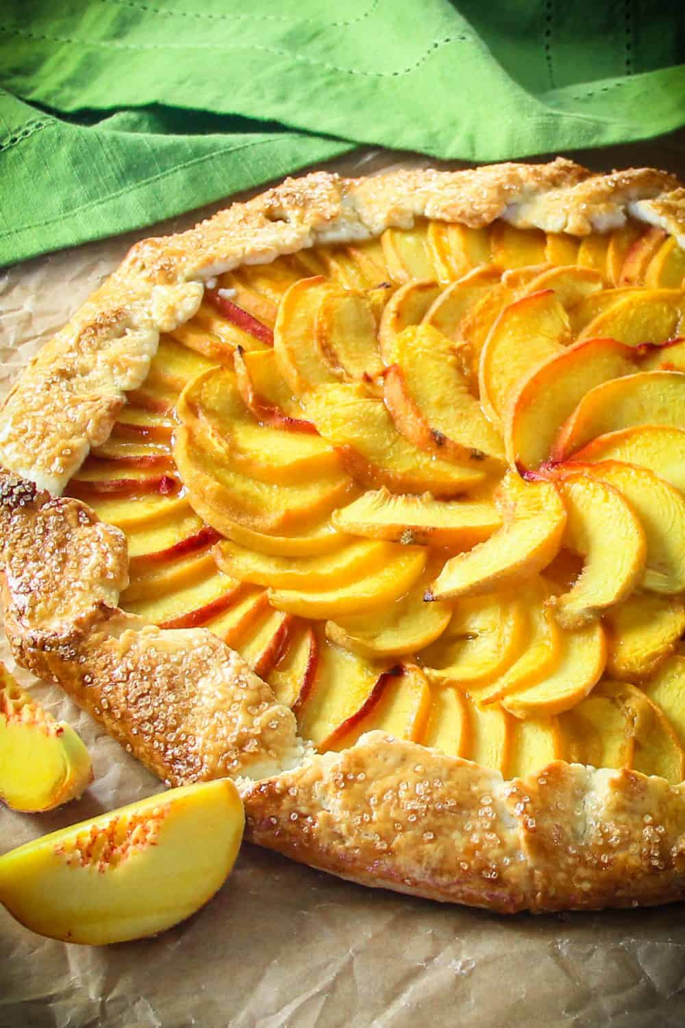 Overhead picture of the baked peach galette laying on brown paper with a green napkin in the background and sliced beaches beside it