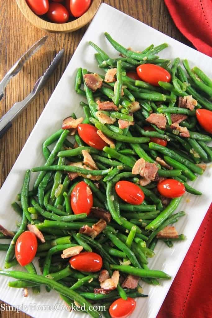 Green bean salad with bacon and tomatoes on a white plate. Some cherry tomatoes in a small wooden bowl next to the salad. Some tongs next to the salad.