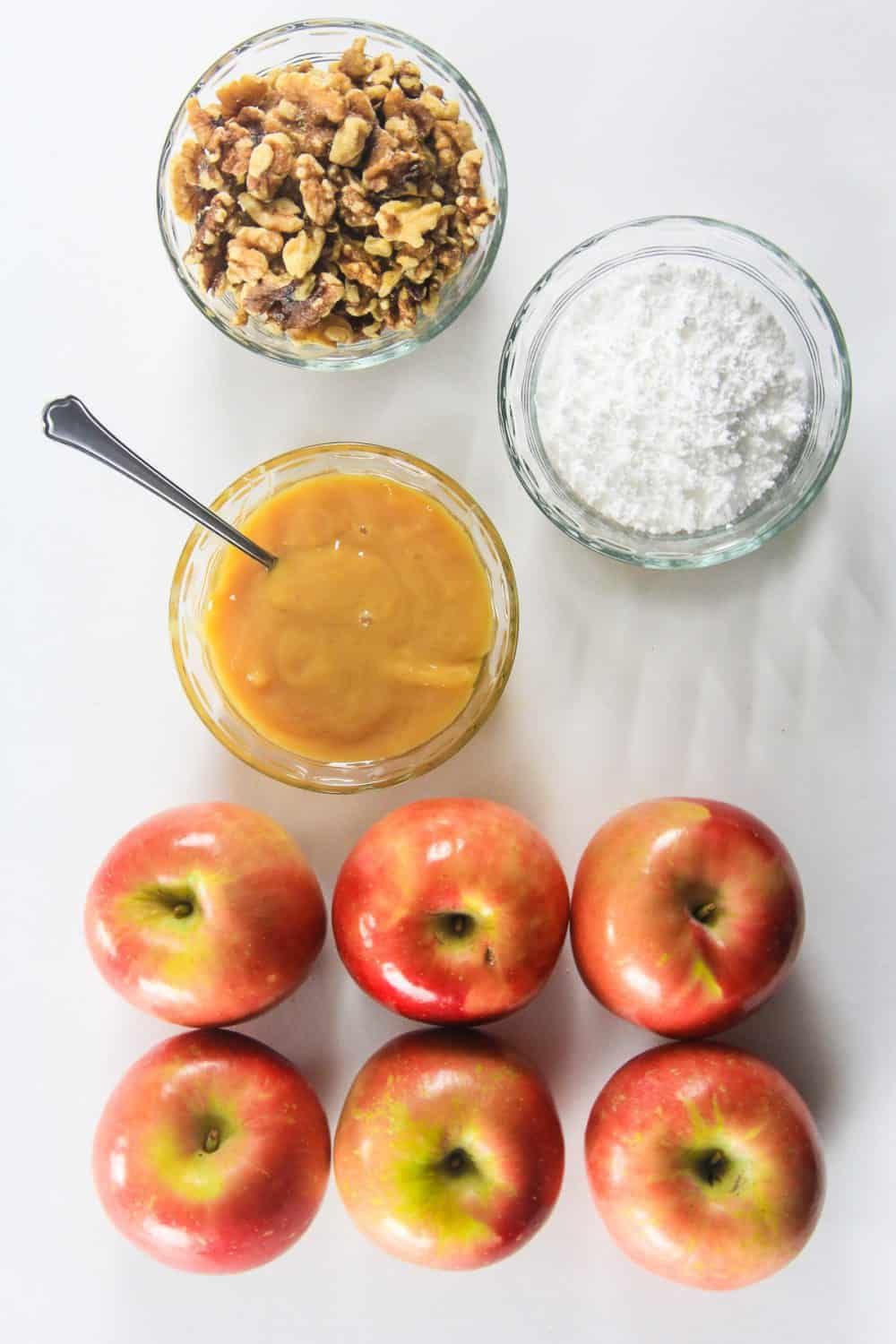 walnuts, powdered sugar, sweetened condensed milk, and apples. Ingredients for baked apples.