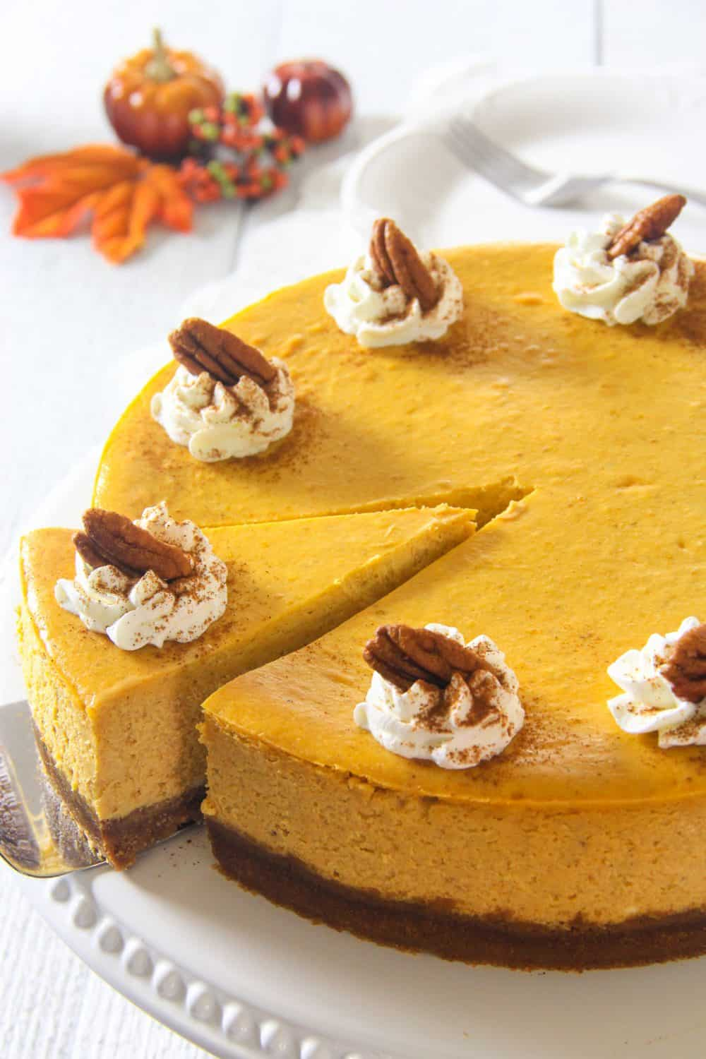 close up image of a homemade pumpkin cheesecake with whipped cream and pecan on top