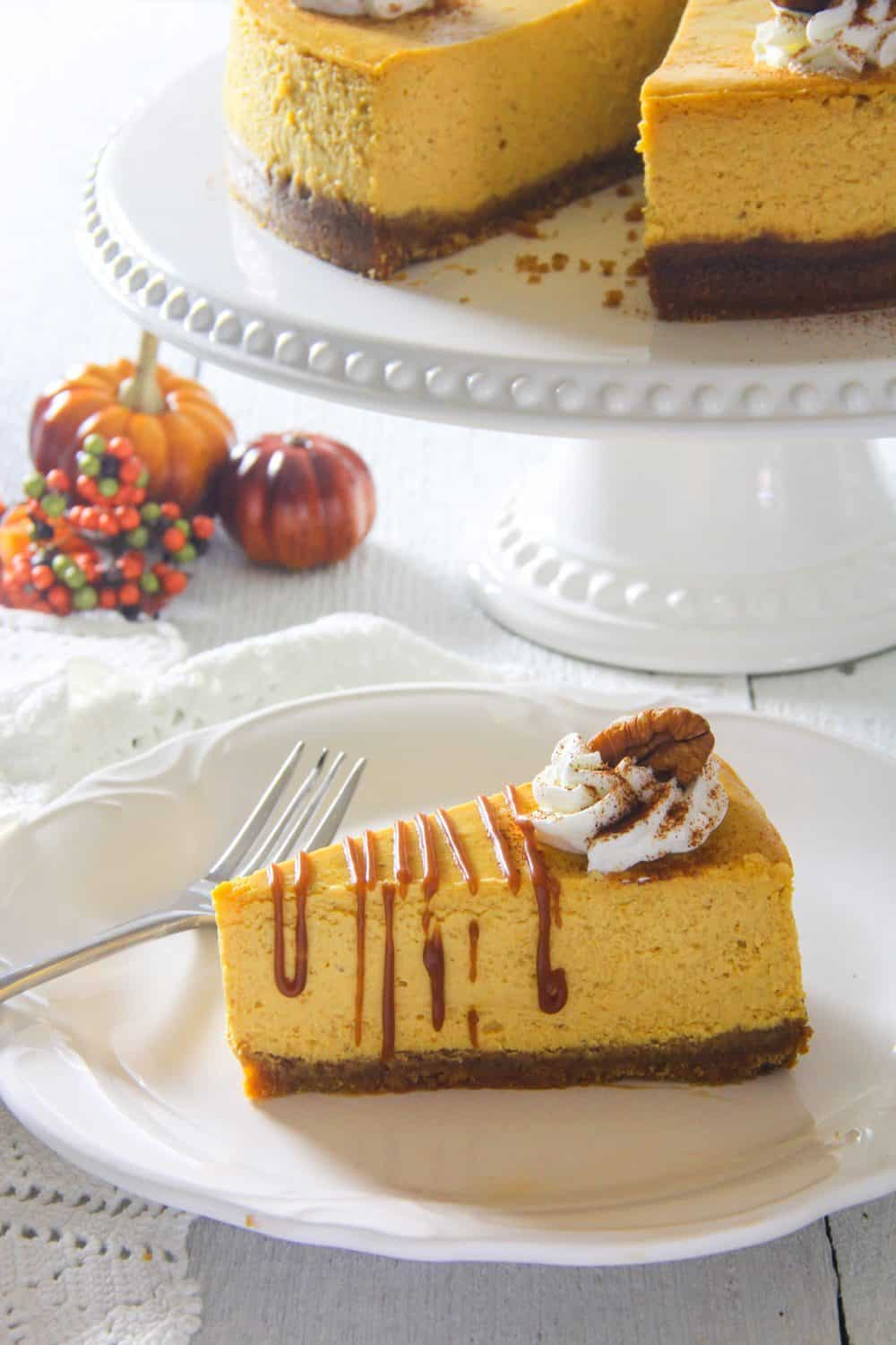close up image of a homemade pumpkin cheesecake with whipped cream and pecan on top and small pumpkins in the background