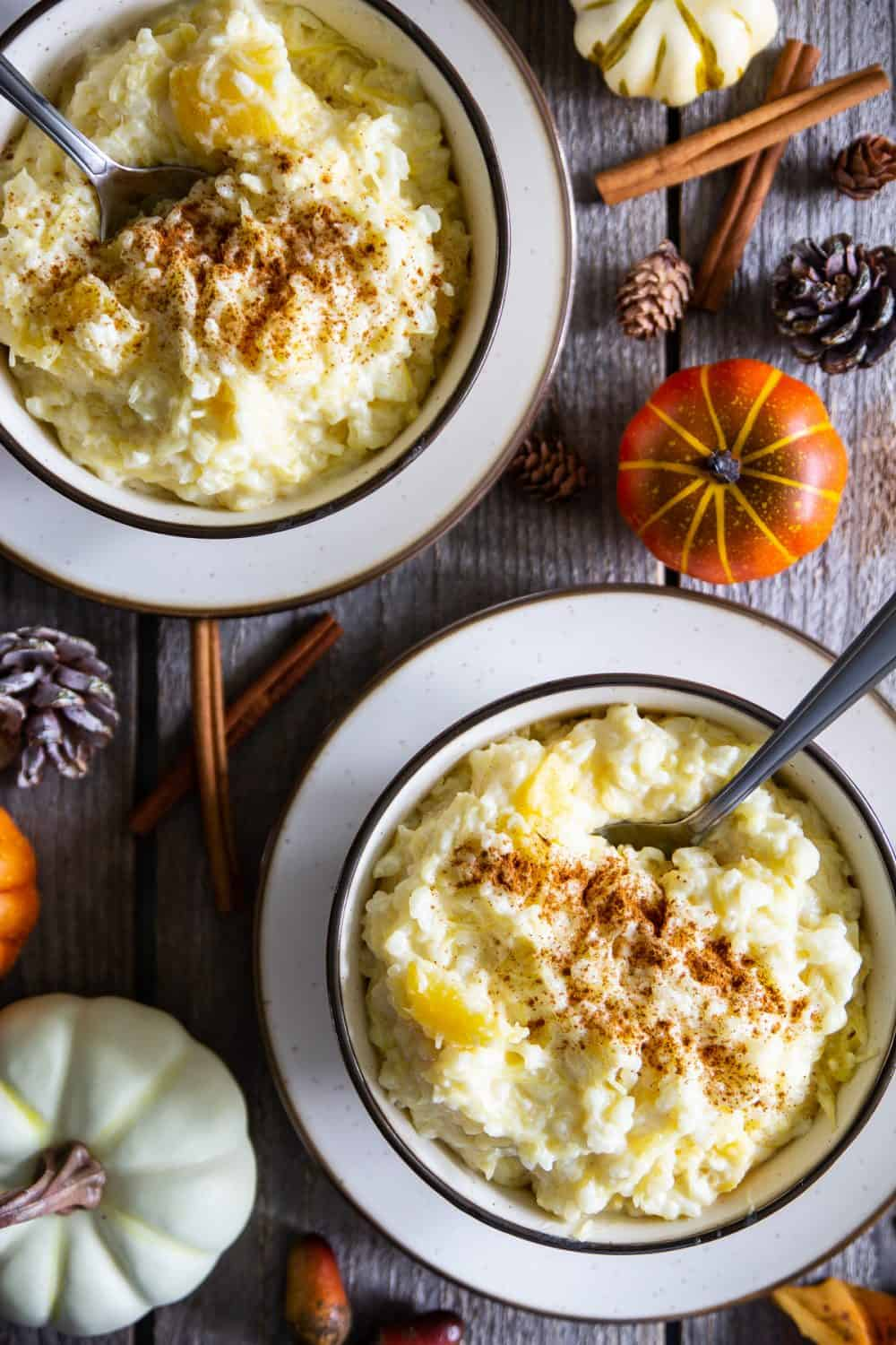 an overhead image of two bowls of rice pudding with cinnamon sticks and mini pumpkin beside them on a dark wooden background