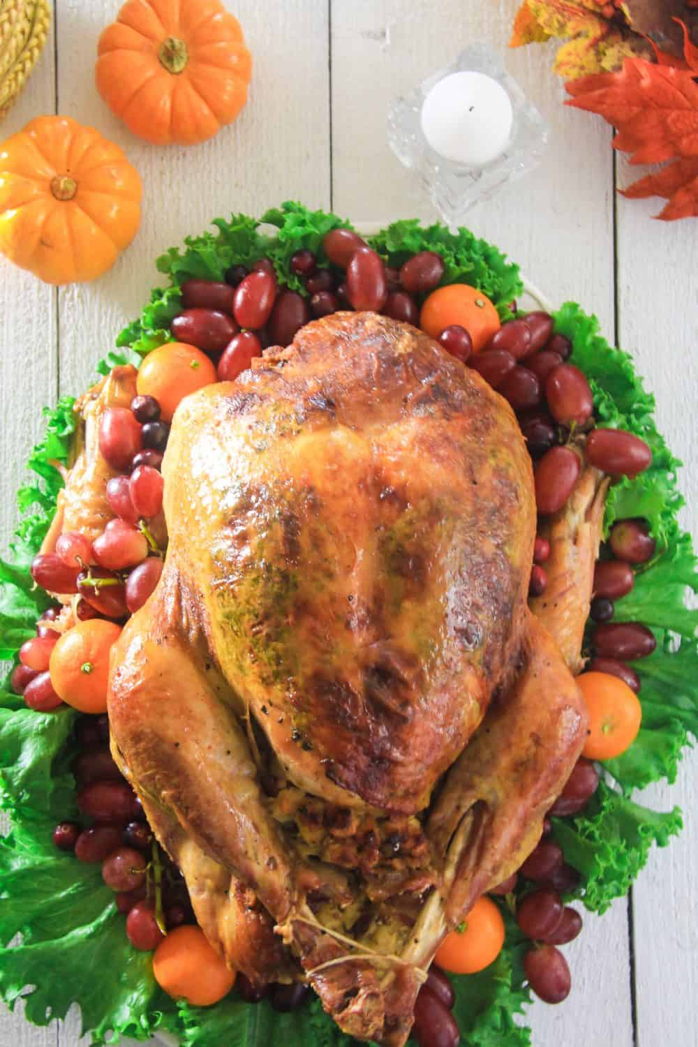 an overhead image of a whole roasted turkey on a white wooden background with grapes, pumpkins and Mandarins around it