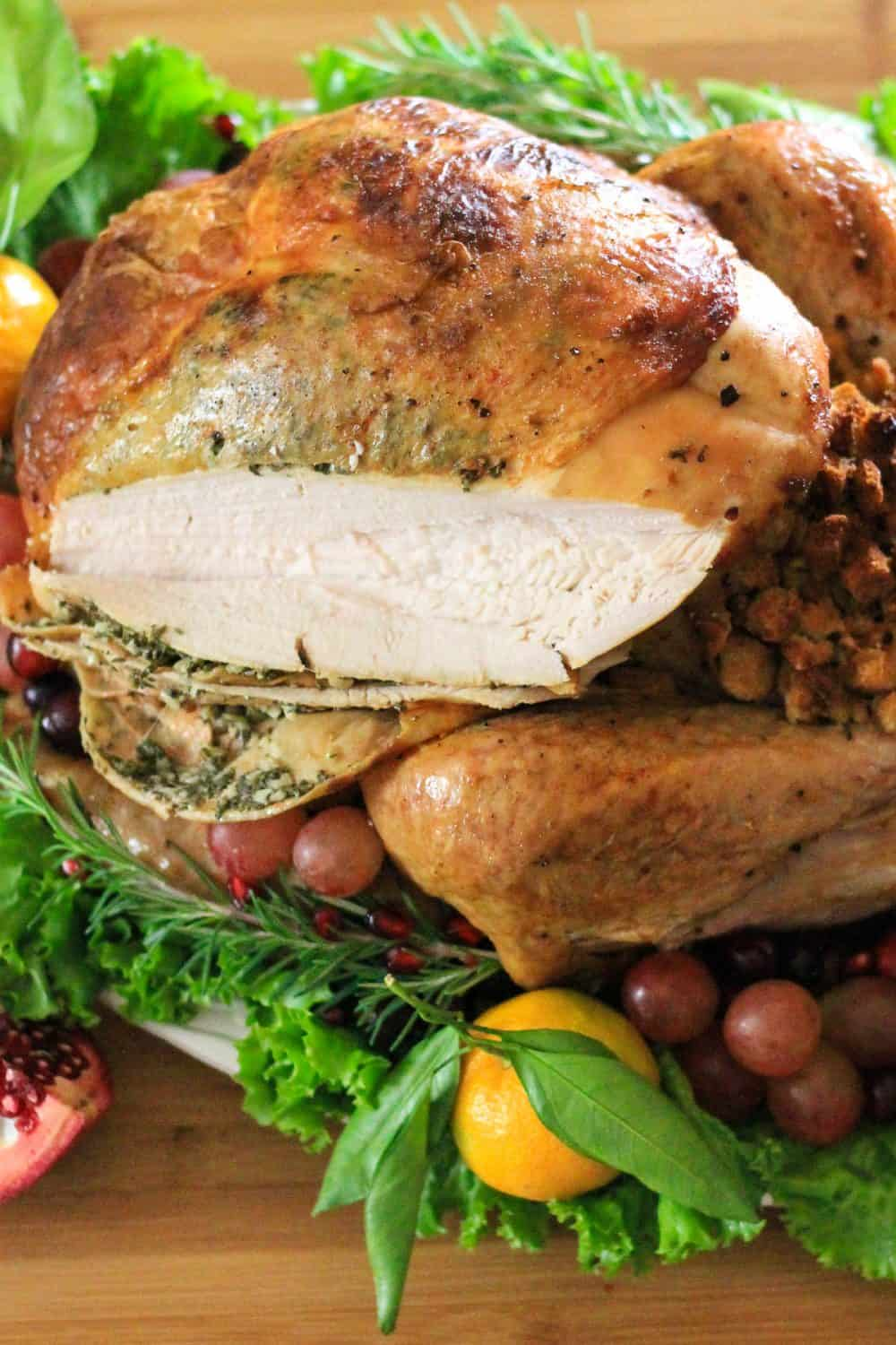 a close up image of a roasted thanksgiving turkey sliced open with rosemary and grapes beside it
